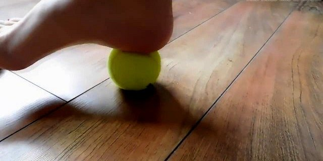 Hannah rolling a tennis ball with her long toes