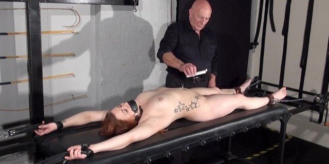 Amateur slave Louise in dungeon rack bondage and hot wax tit