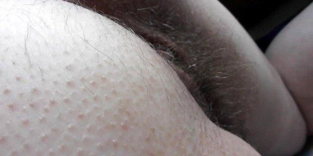 Hairy mature flashing in front of window